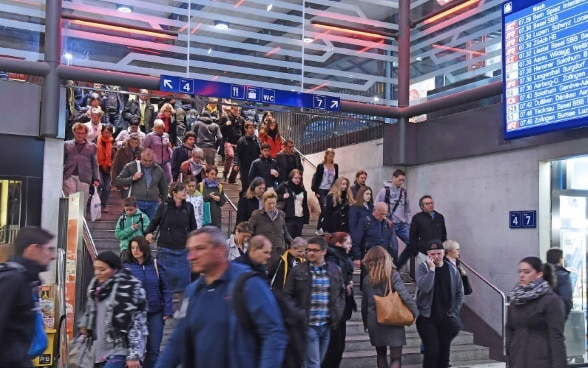 People walking down a busy stairway in a railway station.