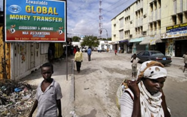 Local residents of a poor area of an African town walking along an empty street in front of a sign saying 'Global Money Transfer'.