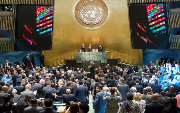 In the general assembly hall of the UN in New York, the high-level government representatives of the UN member states applaud the adoption of the 2030 Agenda.