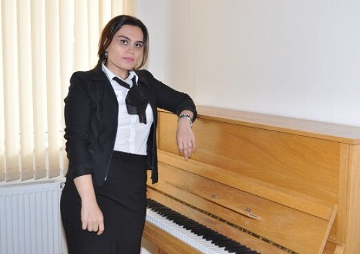 A young azeri woman posing next to her piano