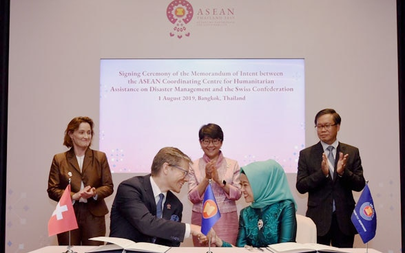 Switzerland's State Secretary Pascale Baeriswyl (left), Thailand's Permanent Secretary Busaya Mathelin (middle) and ASEAN Deputy Secretary General Hoang Anh Tuan (right) witnessing the signing of a Memorandum of Intent between Switzerland and the ASEAN Coordinating Centre for Humanitarian Assistance on Disaster Management (AHA Centre).