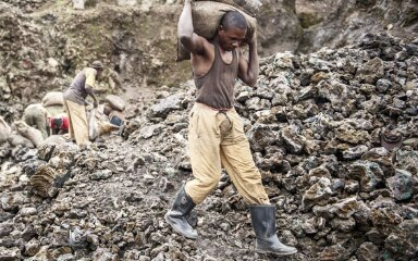 A worker in a cobalt mine in the province of Katanga in the DR Congo transports two sacks of freshly mined ore (13.01.2011). © Keystone