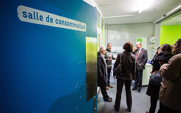 A group of visitors listens as a senior staff member explains something in the drug consumption room in Quai 9.