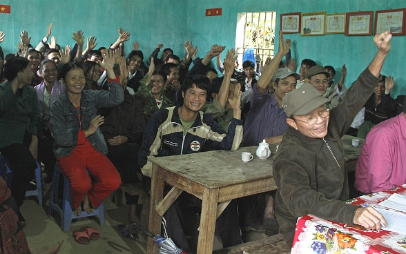 Villagers gathered in a room vote with a show of hands.
