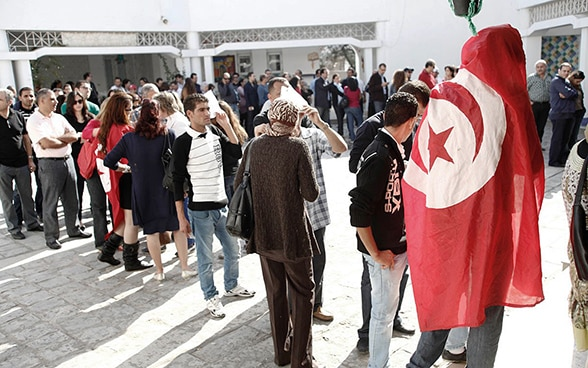 A long queue of people waiting in front of a polling station in Tunisia. A person in the foreground is wrapped in a Tunisian national flag.