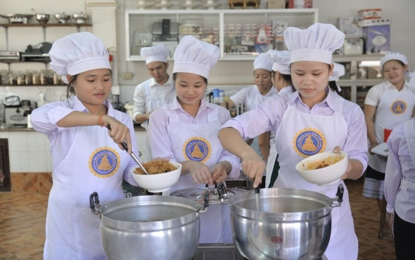 A group of young Laotians, wearing aprons and toques, ladling food from two large pots.