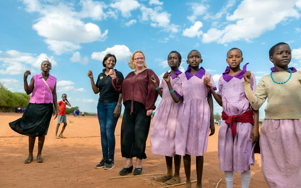Katja Iversen participating and dancing with African girls in a ceremony in Kenya.