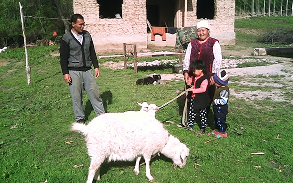 Nurdinov Jeenbek's family with the goat that he received through the project.