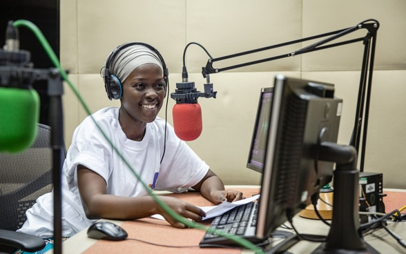 A female African radio presenter makes an entertaining radio show. She uses a red microphone and a computer.