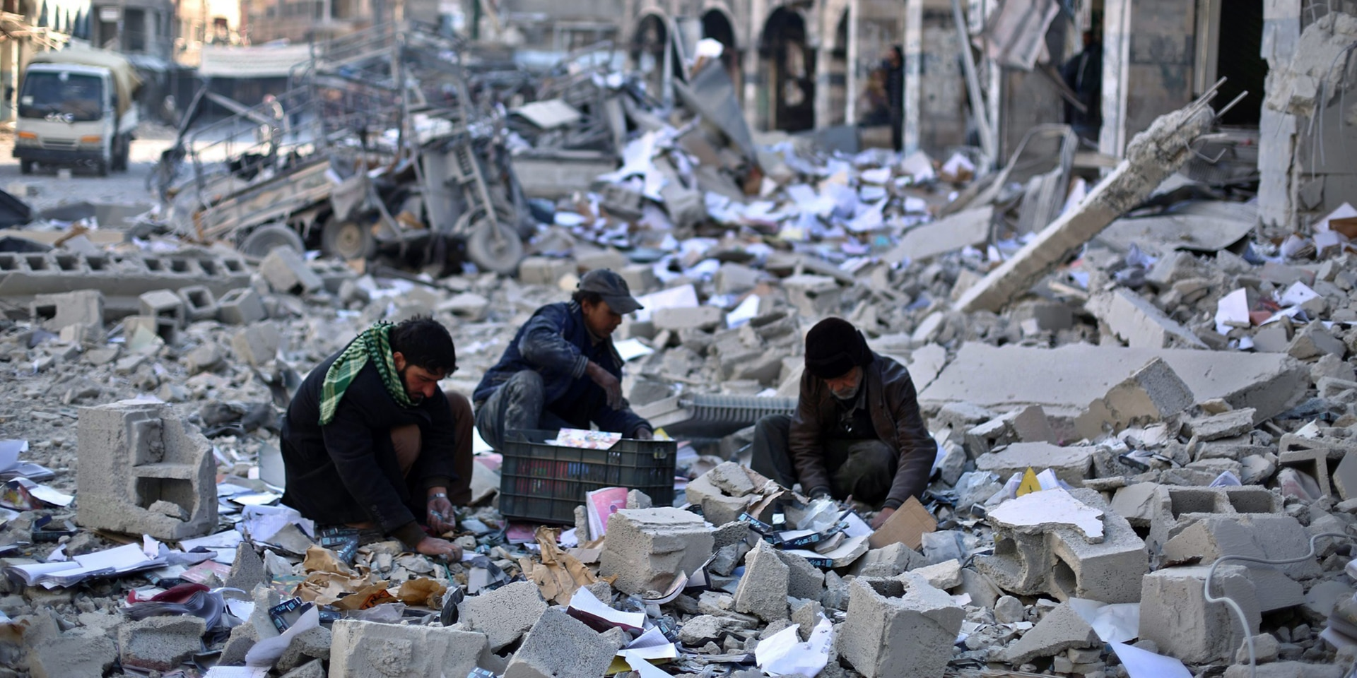 Three men, surrounded by a sea of rubble, pick through the debris of a building destroyed in an air strike.