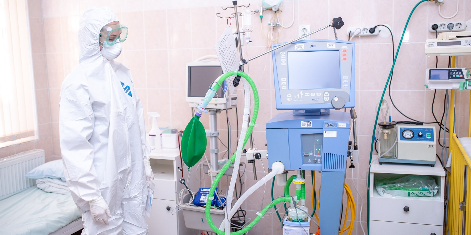 A woman in a hospital room wearing a protective suit, goggles and mask, standing next to hospital equipment.