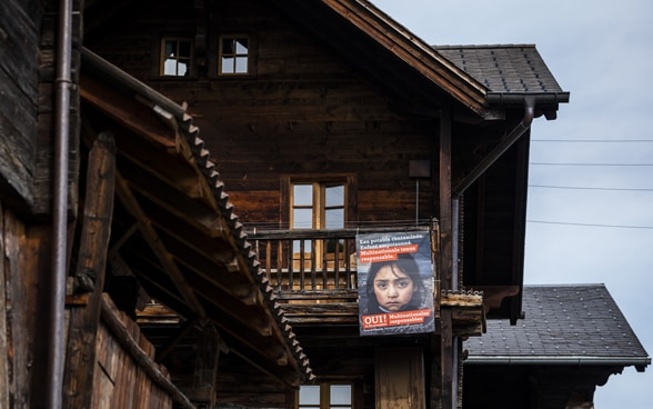 An orange referendum poster for the 'Responsible Business Initiative' on an old mountain barn made of dark wood.
