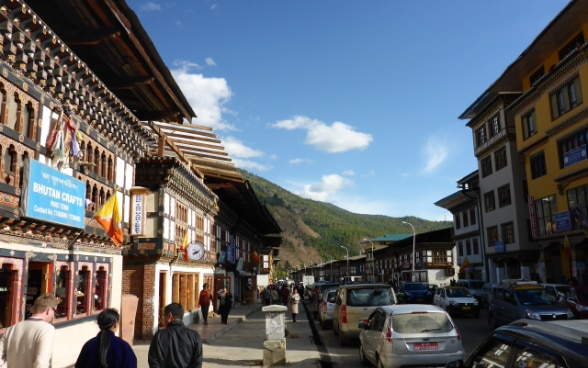 A Swiss visitor walking along a street with two local people in the Bhutanese capital, Thimpu