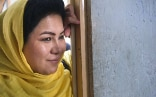 A smiling Afghan woman wearing a traditional yellow headscarf leans on a door frame.