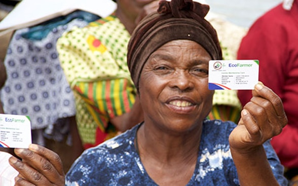 African farmer holding up her Agri-Fin Mobile membership card.