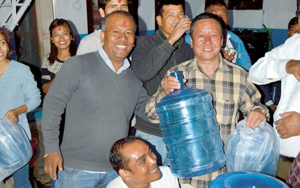 A group of people celebrating their access to drinking water through improved technology.