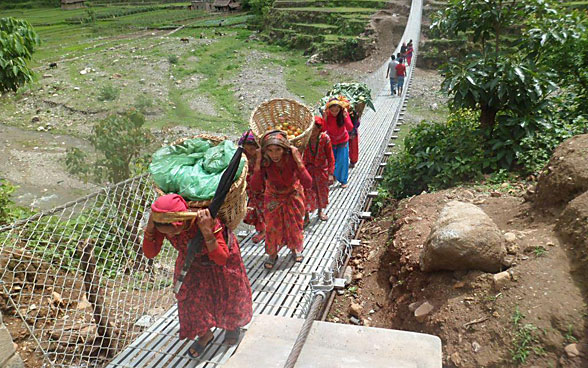 Women carrying baskets walk on a trail bridge.