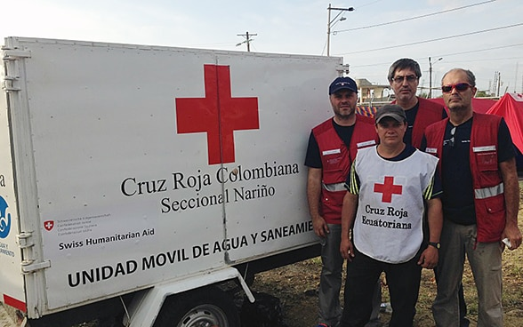 Three members of the Swiss Humanitarian Aid Unit and an Ecuadorian Red Cross worker stand in front of a trailer transporting drinking water.
