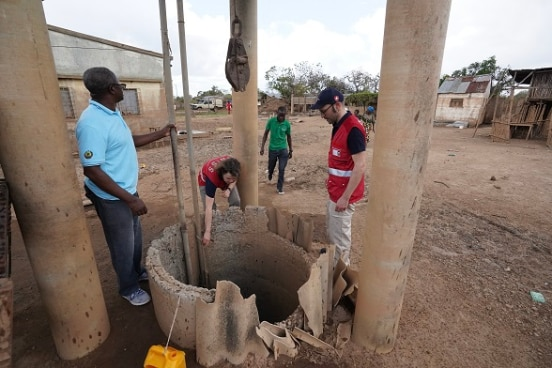 two SHA specialists and their local partners inspects a well