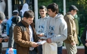 Two young men talk to a passer-by and hand him a leaflet.