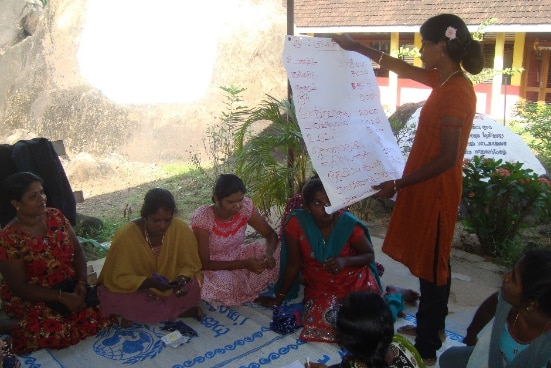 A Sri Lankan woman reading from a large sheet of paper to a group of seated women.