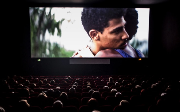 Two men embracing on the screen in a darkened cinema.