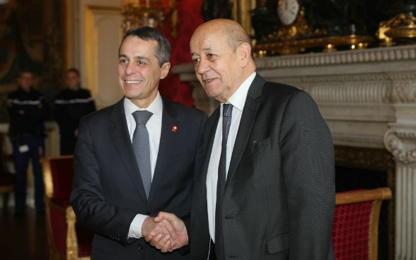 Ignazio Cassis shakes hands with French Foreign Minister Jean-Yves Le Drian in Paris.