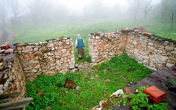 A woman in Bosnia leaves her destroyed house. © Keystone