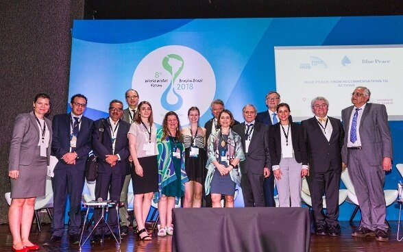 Six women and nine men of different nationalities in front of a blue wall with the logo of the World Water Forum in Brasilia.