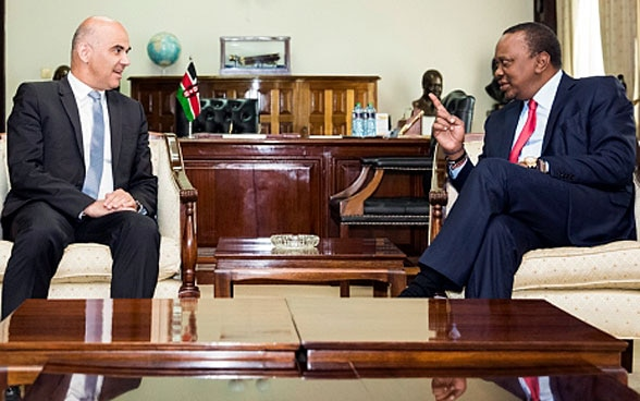 President Berset and Kenyan President Kenyatta sit at a wooden table and discuss.