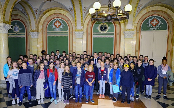 Around 80 children pose for a group photo. In the middle is Federal Councillor Ignazio Cassis.