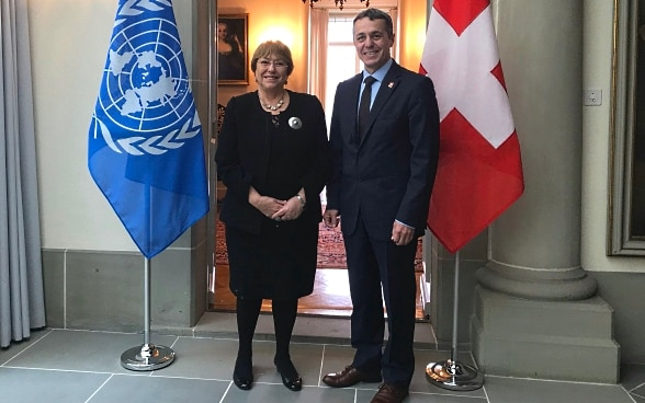 Federal Councillor Ignazio Cassis and the UN High Commissioner for Human Rights Michelle Bachelet pose for a photo. In the background you can see the flags of Switzerland and the UN.
