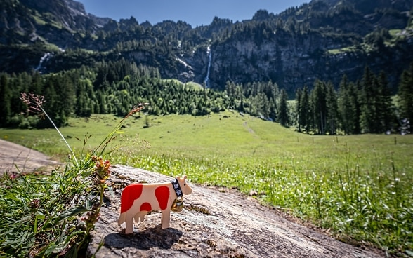 A red spotted cow made of wood stands in a Swiss mountain landscape.