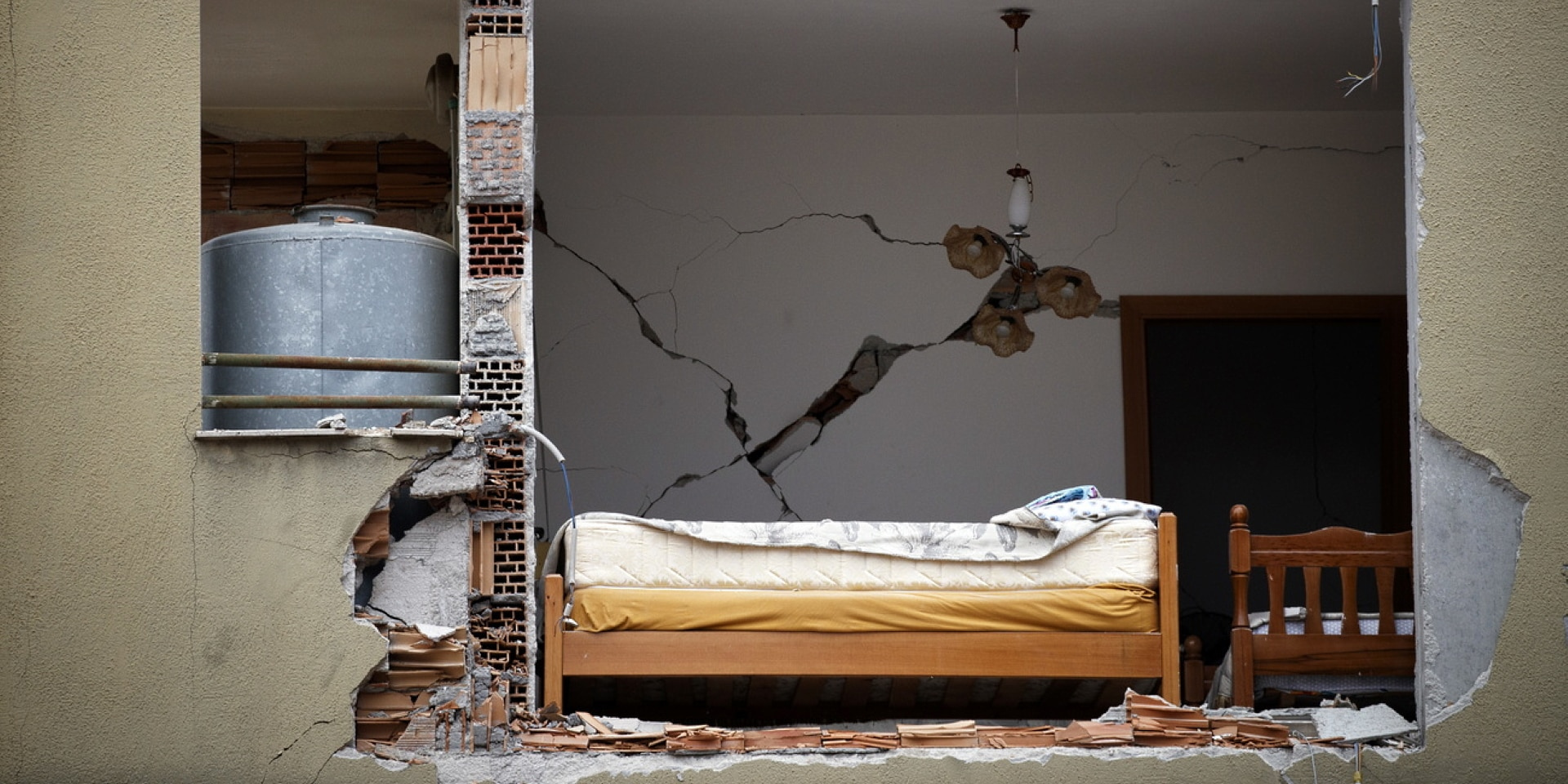 The earthquake tore open the front a building, where a bed is now visible.