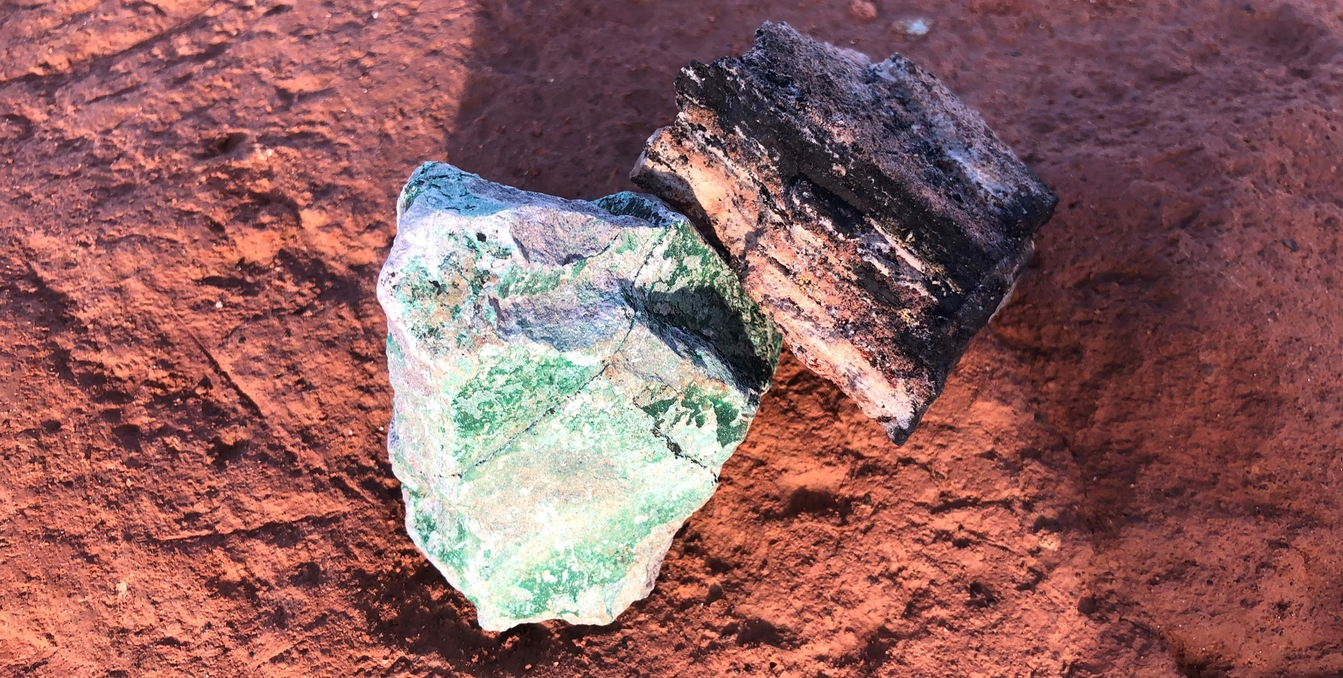 A black piece of cobalt and a green piece of copper placed on the ochre soil to symbolise the mining industry in the Democratic Republic of the Congo's Copperbelt region.