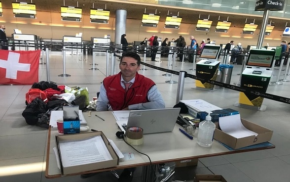 In the check-in hall at Bogotá airport, a member of the Swiss embassy in Colombia is sitting behind a table and a computer to assist travellers.