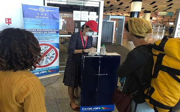 Two Swiss women carry out administrative formalities at Dakar airport before boarding a return flight to Switzerland.