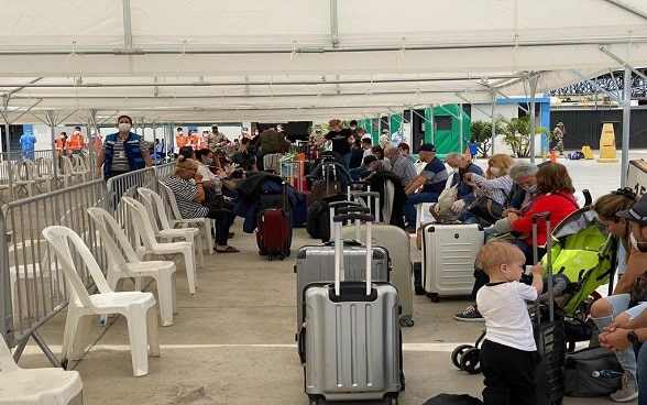 Travellers wait in a tent on the tarmac at Lima Airport in Peru before boarding the next flight to Zurich.