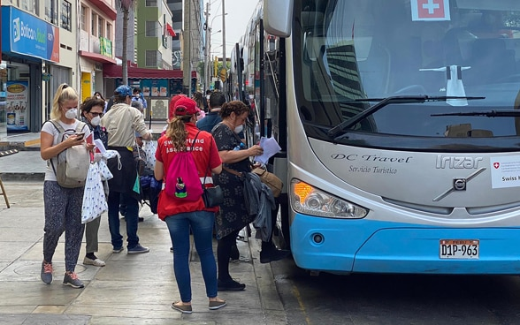 Several tourists board a bus organised by the Swiss Embassy. It takes them to Lima.