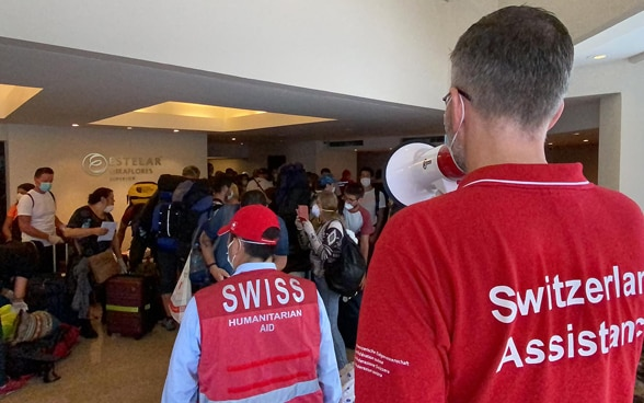 An employee of the Swiss Embassy gives instructions to the travellers with a megaphone.