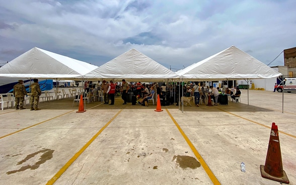 Tents are located at the airfield of the airport of Lima. Below them are the passengers of the return flight to Zurich.