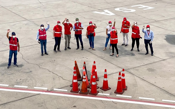 View from the plane to a group of embassy staff in red jackets standing and waving on the airfield.