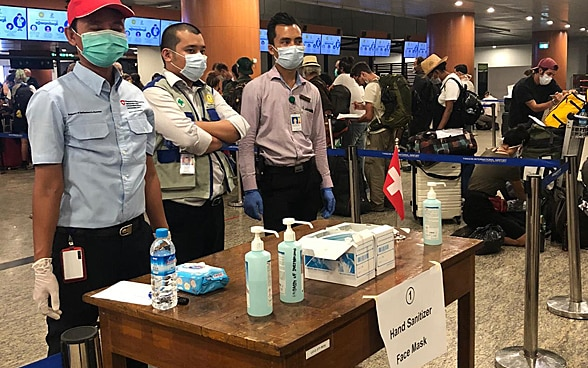 Three employees of the embassy are standing at a table with hygiene and disinfectant products.