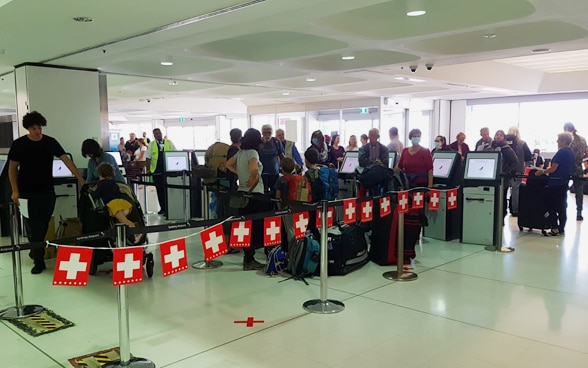 In the check-in hall of Sydney Airport, a garland of small Swiss flags immediately indicates where the right check-in counter is located.