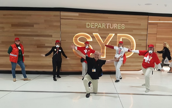 Staff of the Swiss Consulate General in Sydney pose in front of an illuminated sign indicating the departure hall.