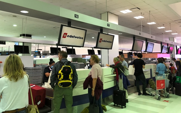Passengers are at the check-in counter to check in for the Sydney-Zurich flight.
