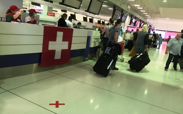The square Swiss flag is displayed at a check-in counter at Sydney Airport.