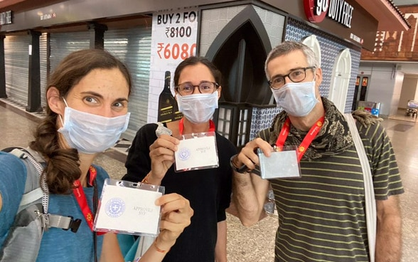 Three passengers wearing masks proudly display their Indian customs clearance badges to board the next flight to Switzerland.