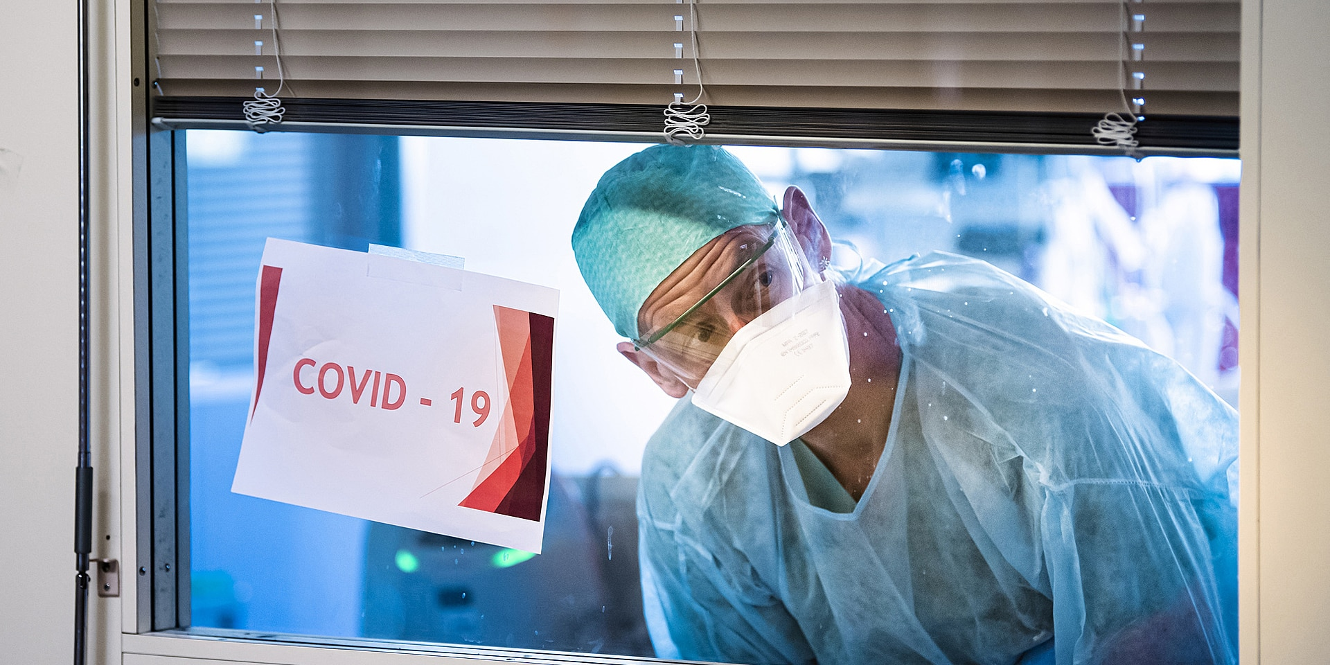A health worker looks through an intensive care unit window past a taped-on paper sign that says 'COVID–19'.
