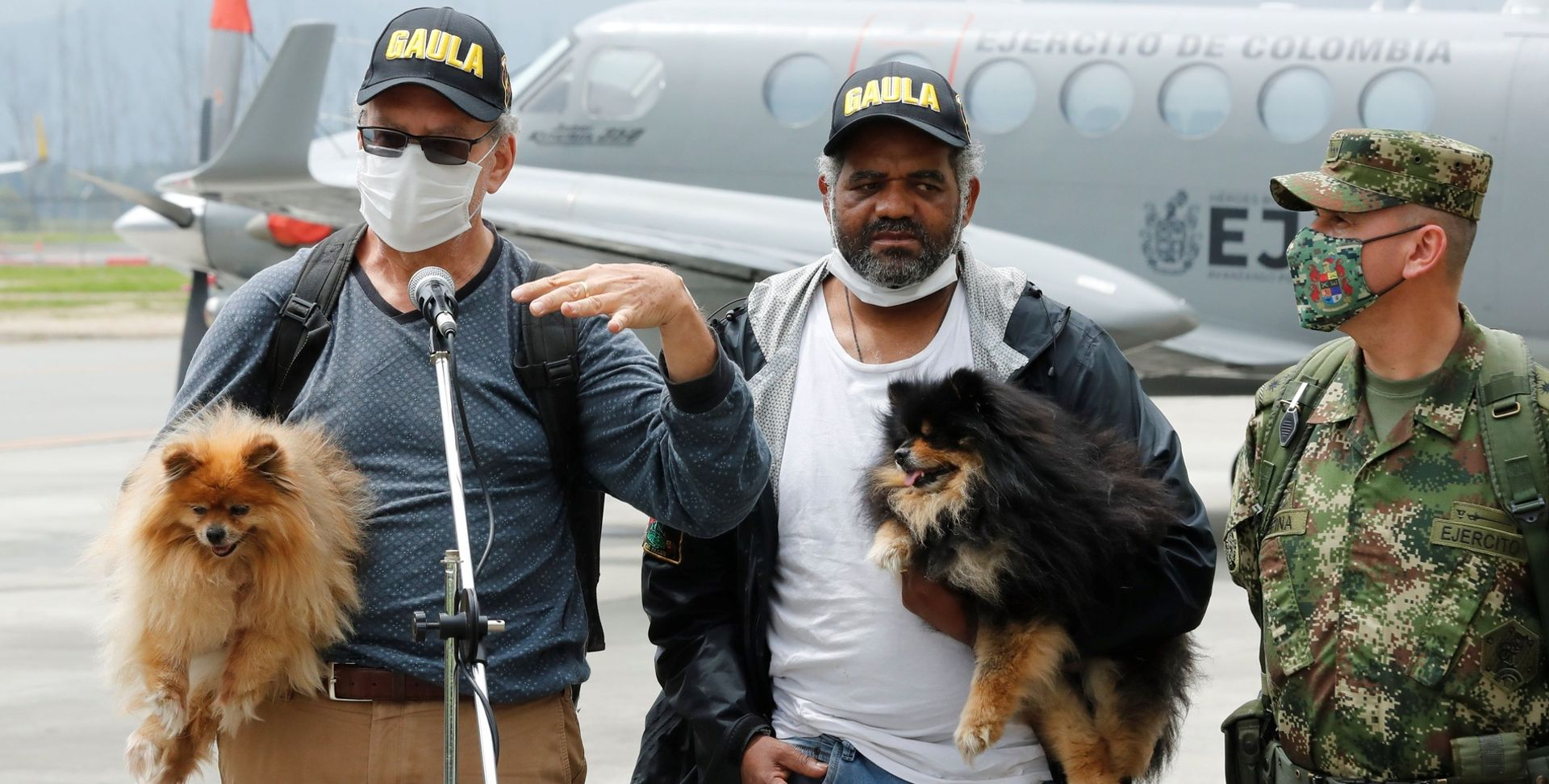 Two men with small dogs on their arms stand in front of a microphone at a military airfield and give a press conference. On the right is a Colombian soldier.